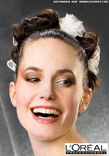 Gesteckter Dutt aus Haarschlaufen mit zarten Blüten