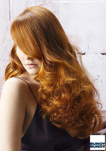 Glattes, rotes Haar ergießt sich asymetrisch in prachtvollen Locken