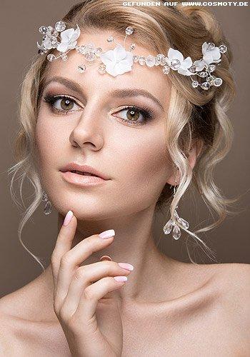 Hochgesteckte Brautfrisur mit gewellten Strähnen zum Glasperlen-Kranz