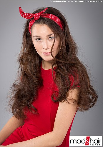 Mädchenhafter Frisurenlook mit rotem Haarband in den lockigen Haaren
