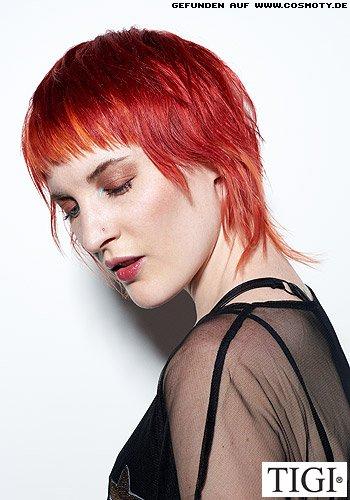 Stark fransig geschnittener Kurzhaarschnitt in sattem Rot mit Strähnen in Orange
