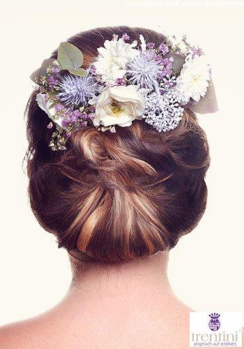 Üppig geschlungener Chignon mit extravaganten Blüten