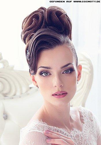 Zu opulenten Rosetten hochgestecktes Haar