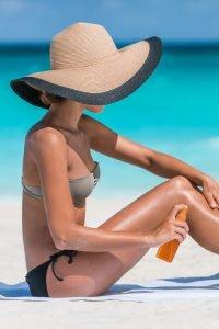 Frau cremt sich am Strand ein