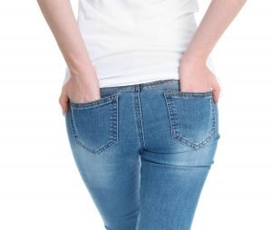 frau mit jeans, die pickel am po verursacht, von hinten