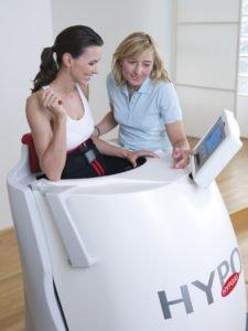 Eine Frau trainiert mit einem Hypoxi Gerät im Sitzen
