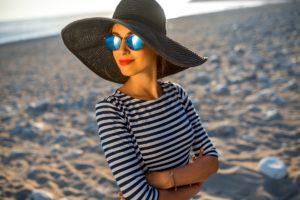 Frau sitzt mit Sonnenhut und Sonnenbrille am Strand