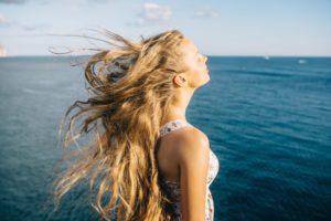 Eine Frau steht am Meer und der Wind weht durch ihre Haare