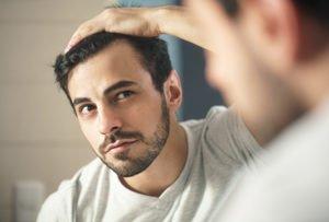mann untersucht seine haare