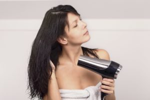 Frau mit strähnigen Haaren beim Föhnen