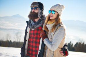 Pärchen läuft im Schnee mit Sonnenbrillen