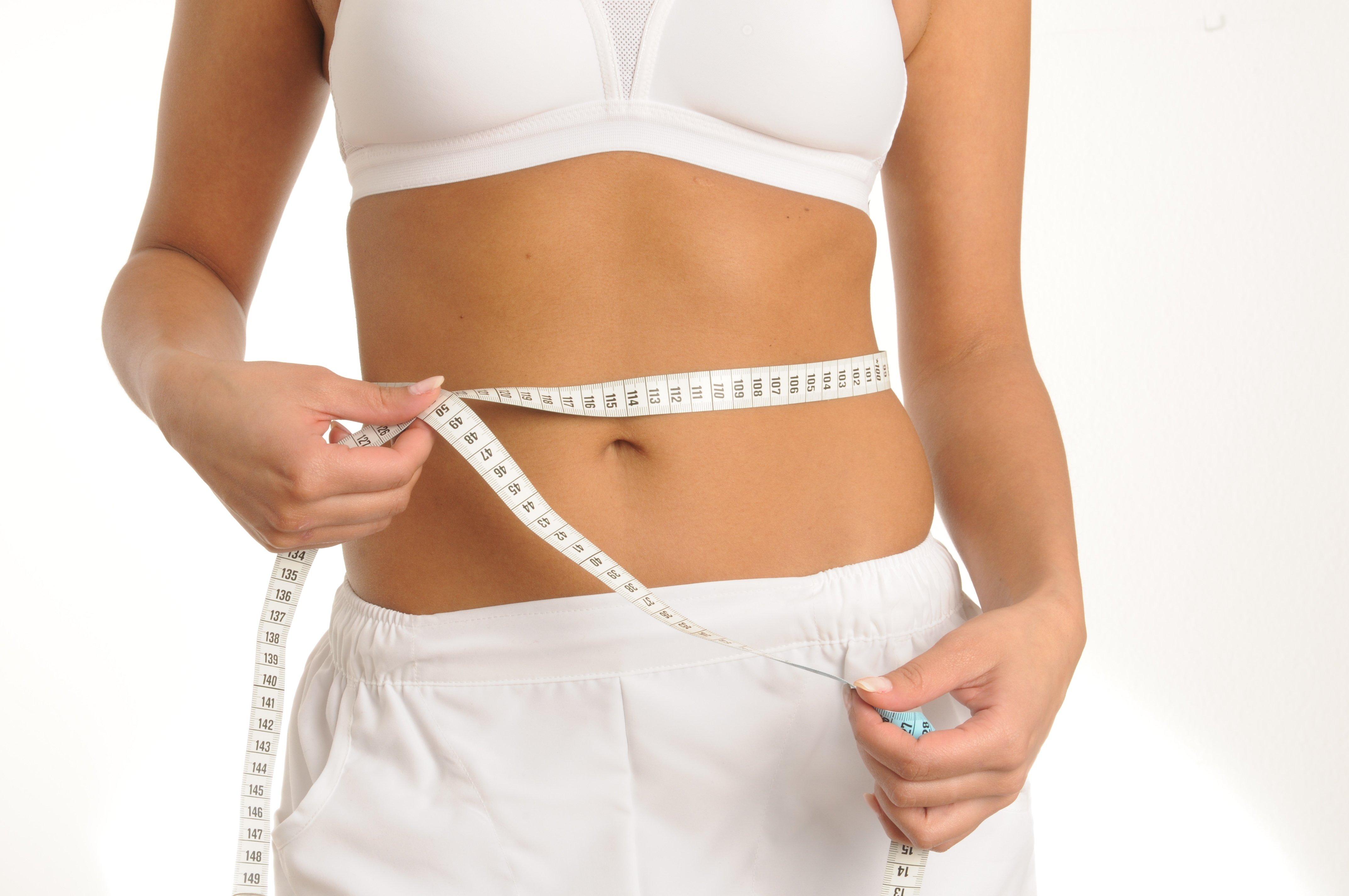 Frau misst ihren Körperumfang für Hypoxi