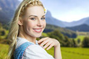 attraktive blonde Frau im Dirndl vor Alpen-Hintergrund