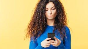 Frau blickt skeptisch auf ihr Smartphone