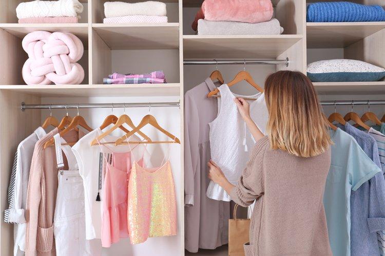 Frau steht vor Kleiderschrank