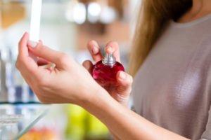 Hand sprüht Parfum auf Handgelenk