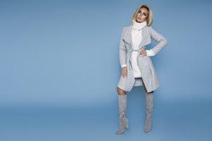 Frau in kurzem Kleid mit Mantel und hohen Stiefeln