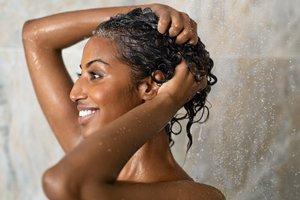 lächelnde Frau shampooniert sich die Haare