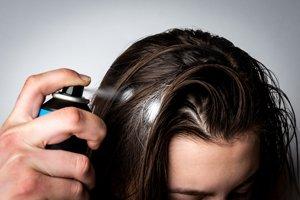 Frau benutzt Trockenshampoo am Haaransatz