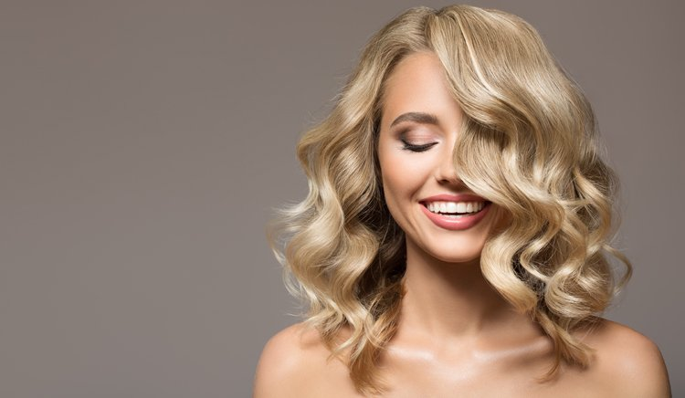 Frau mit schulterlangen gewellten Haaren lächelt